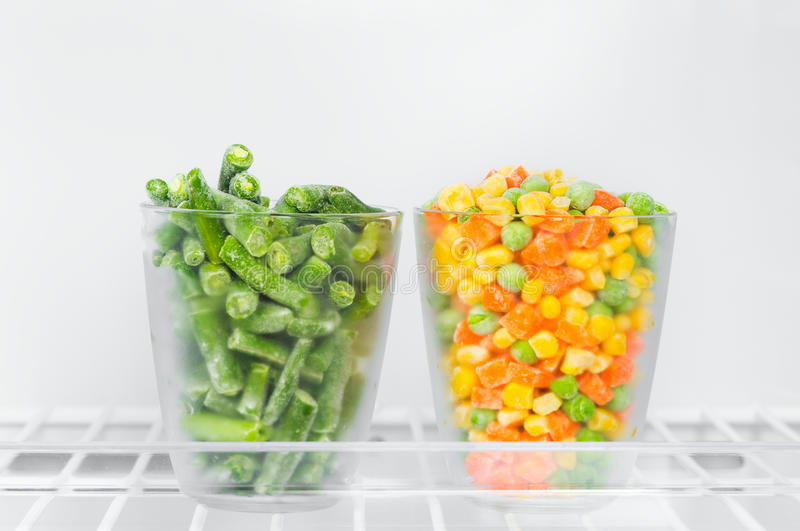 Frozen green beans, corn green peas and chopped carrots in a gl. Frozen vegetables and legumes in the freezer, green beans, corn green peas and chopped carrots royalty free stock photo