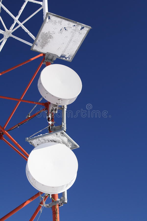 Frozen GSM antenna in blue sky. Detail of a frozen GSM antenna with blue sky as background stock photos