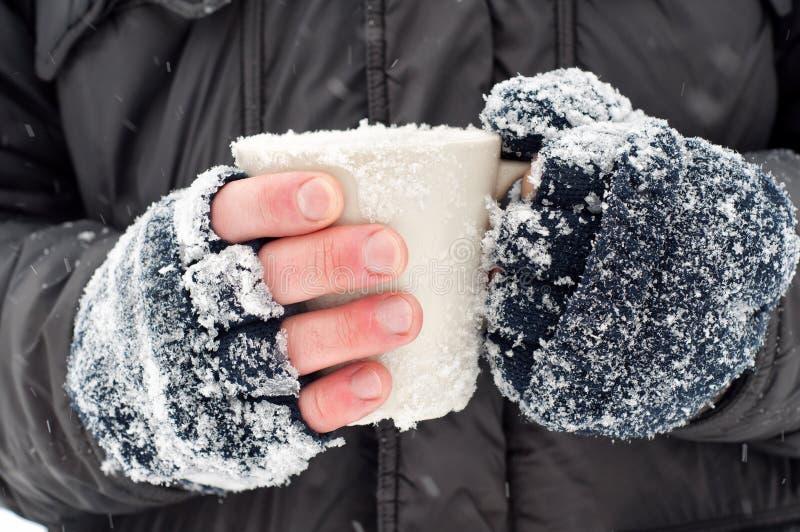 Frozen hands holding a mug stock photos