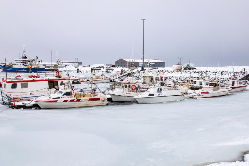 The frozen harbor of the Icelandic fishing village of Höfn in winter, with its boats laid up until the thaw. HÖFN, ICELAND / FEBRUARY 10, 2016: The frozen royalty free stock image