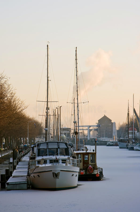 Frozen harbour with ships in winter at sunset royalty free stock photography