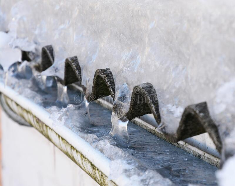 Frozen house roof rain gutter full of ice in winter stock images