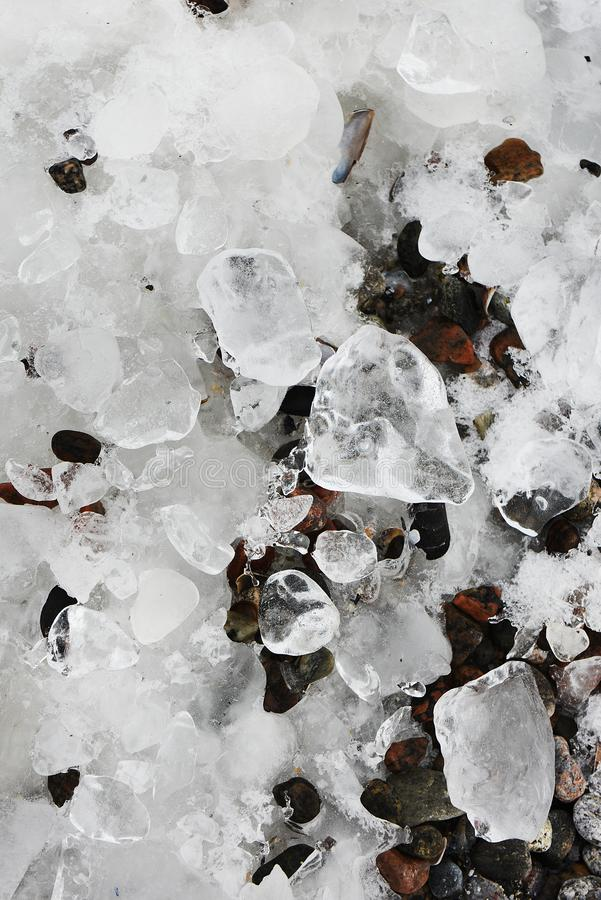 Frozen ice pebbles on the seashore. Winter season. Natural winter background. stock photography