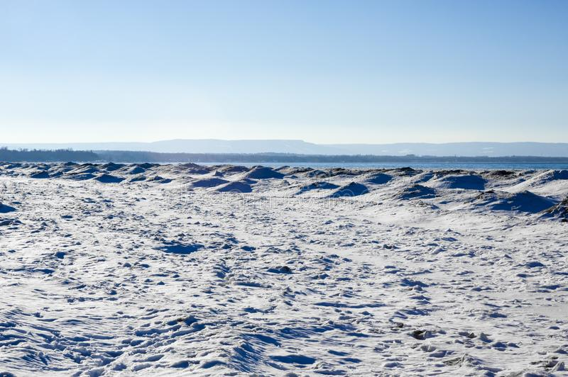 Frozen ice, snow, and sand dunes on beach with hills in distance. Frozen ice, snow, and sand dunes on beach in winter by lake under clear blue sky. with hills in stock photo