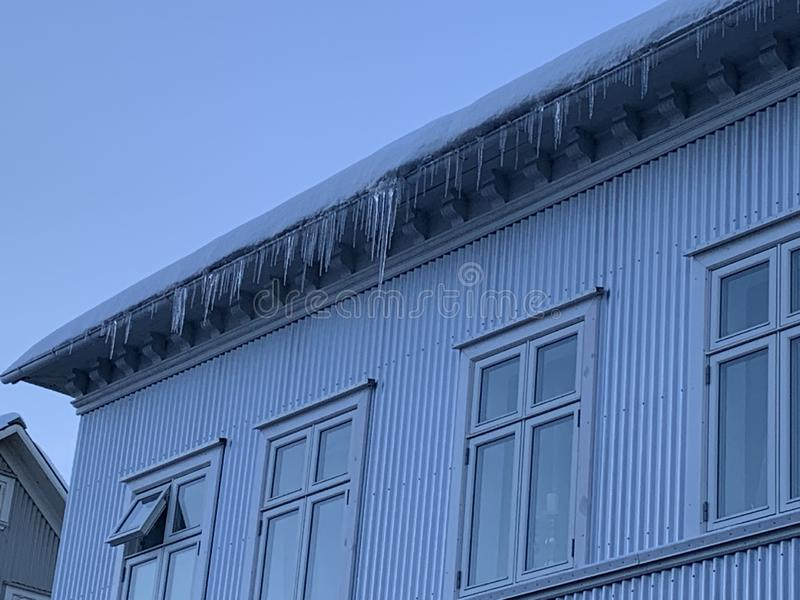 Frozen icicles on houses stock photos