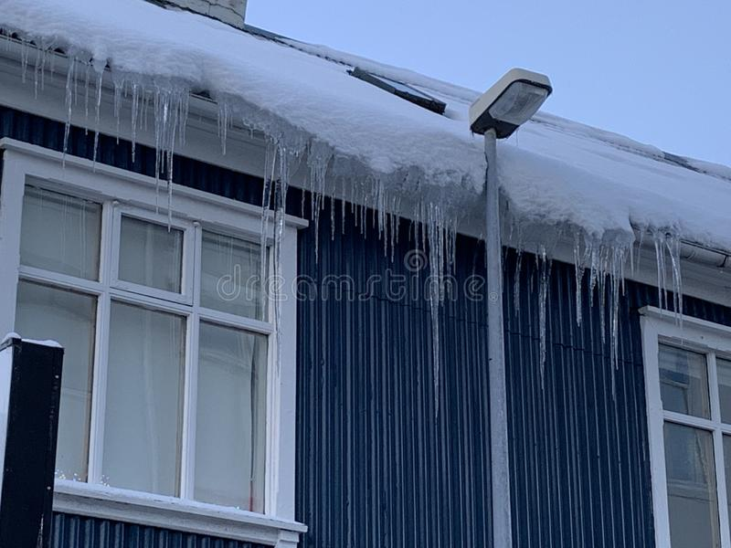 Frozen icicles on houses royalty free stock image