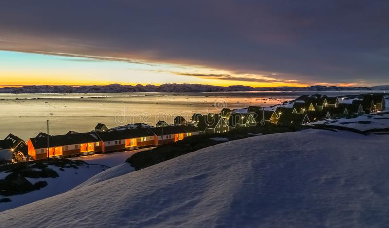 Frozen inuit houses among rocks and snow at the sunset fjord in outskirts of arctic capital Nuuk stock photography