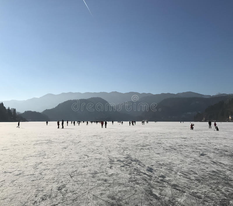Frozen lake Bled many people on ice. Frozen lake Bled unique phenomenon many people on ice walking stock photo