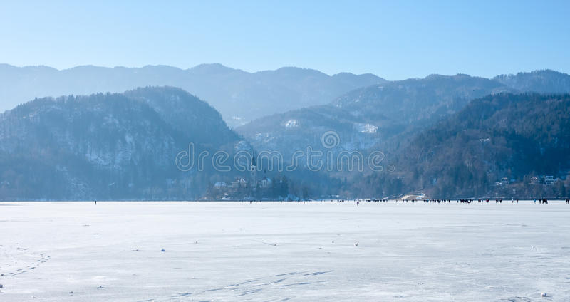 Frozen lake Bled many people on ice. Frozen lake Bled unique phenomenon many people on ice walking royalty free stock photo