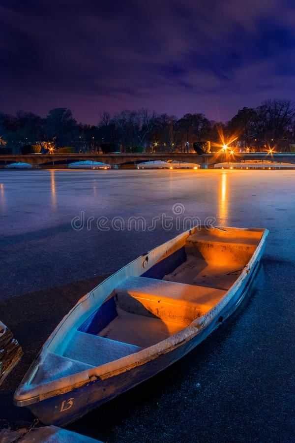 Frozen lake with a boat in the winter shot during night in a par royalty free stock image