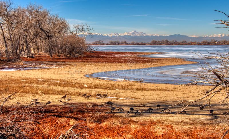 Frozen Lake in Colorado Rockies. Dramatic frozen lake side photo with Colorado Rockies in the background stock photography