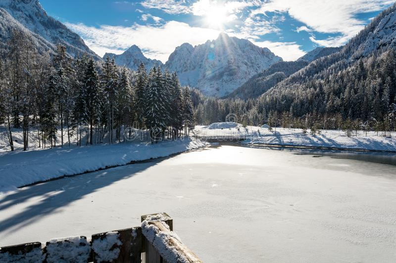Frozen lake Jasna at Kranjska Gora and a view toward mountains. On a sunny winter day stock images