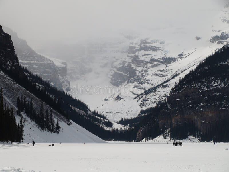 Frozen Lake Louise in winter season. People walking on frozen bed of lake louise during winter cold stock image