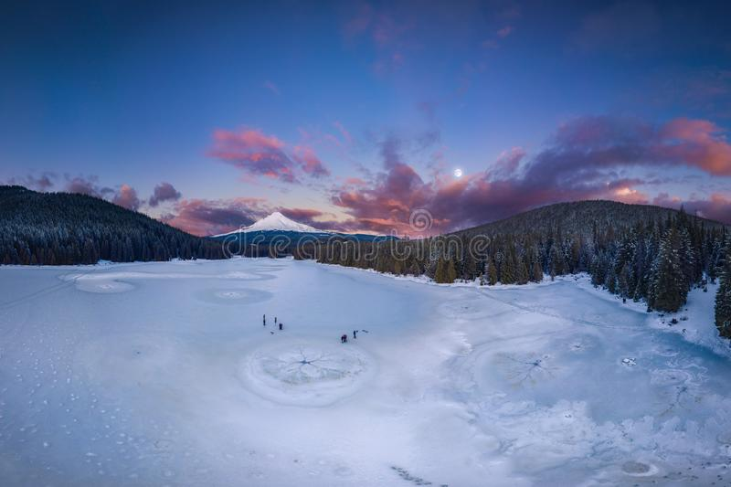 Frozen lake, Mt Hood and full moon. This is a panoramic sunset view of the frozen Trillium Lake and Mt Hood royalty free stock image