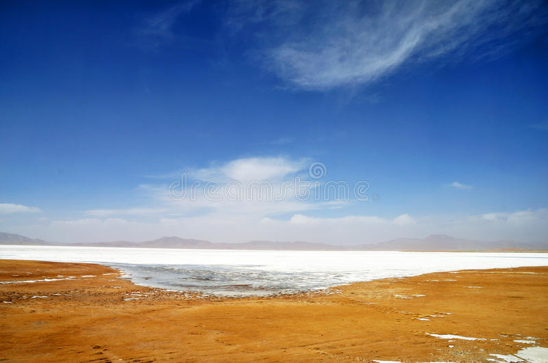 Frozen Lake in Qinghai-Tibet Plateau. Winter Scenery in Qinghai-Tibet Plateau. There are frozen rivers,barren field and snow mountains under blue sky stock image