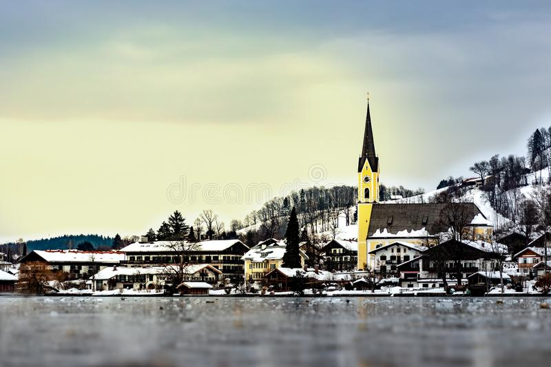 The frozen lake `Schliersee` in Bavaria, germany, in winter with yellow church St. Sixtus and houses with snow in the back royalty free stock image