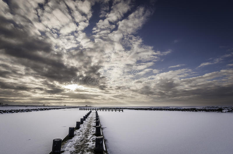 Frozen lake at sunset viewed form a pier. royalty free stock photography