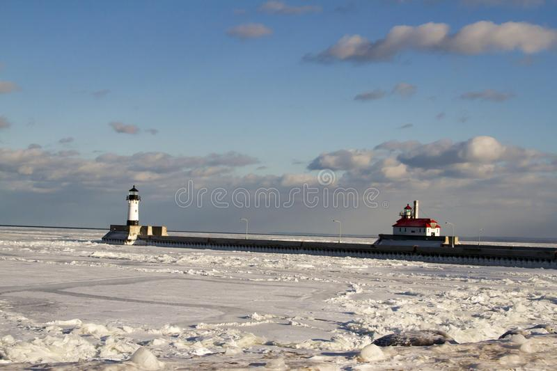 Frozen Lake Superior rocky shoreline with lighthouses and shipping pier in Duluth, Minnesota, USA in winter. Frozen Lake Superior shoreline with lighthouses and royalty free stock image