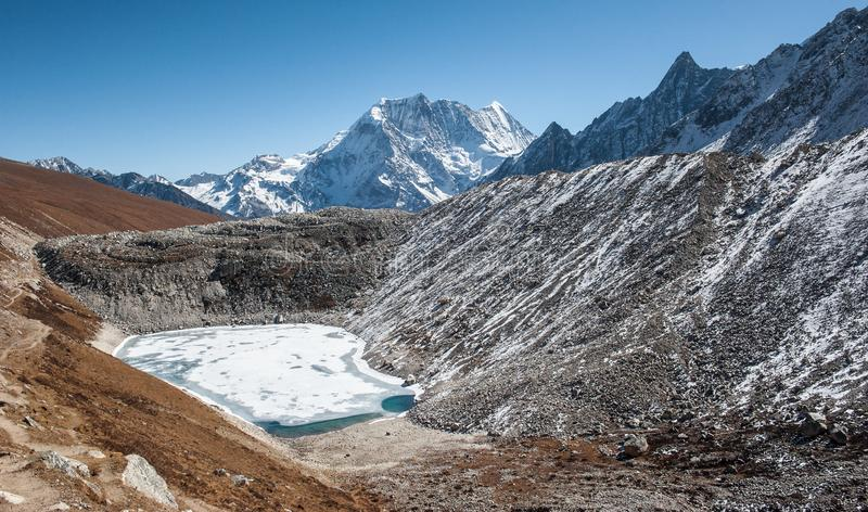 Frozen lake on the way to the pass on Manaslu circuit with view of Mount Manaslu range 8 156 meters. Trekkers in Himalayas. Manaslu Glacier in Gorkha District stock photo