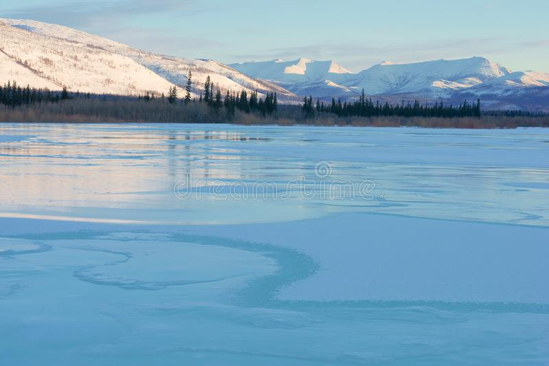 Blue ice of the frozen lake at morning. Winter landscape in the mountains and the winter road in Yakutia, Siberia, Russia. Frozen lake in winter mountains at stock images