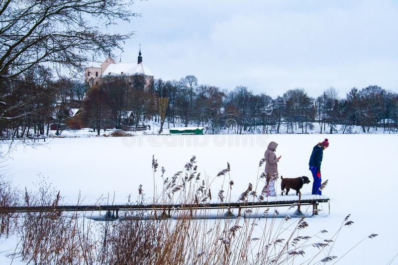 Frozen lake in winter, with pier, people and dog. People with dog on a pier with snow on the frozen lake, forest and church in the background stock photos