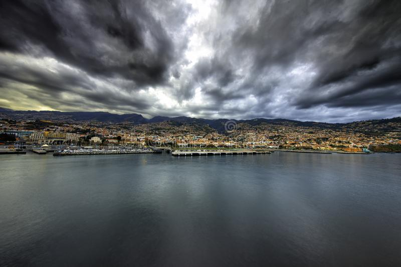 Funchal, Madeira from the sea. The majestic sea shore of Madeira with the capital funchal in the forefront under a stormy sky stock photos