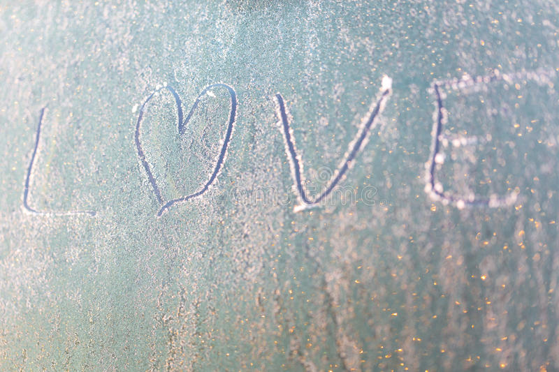 Frozen love on car window with heart shape on frosty windscreen royalty free stock images