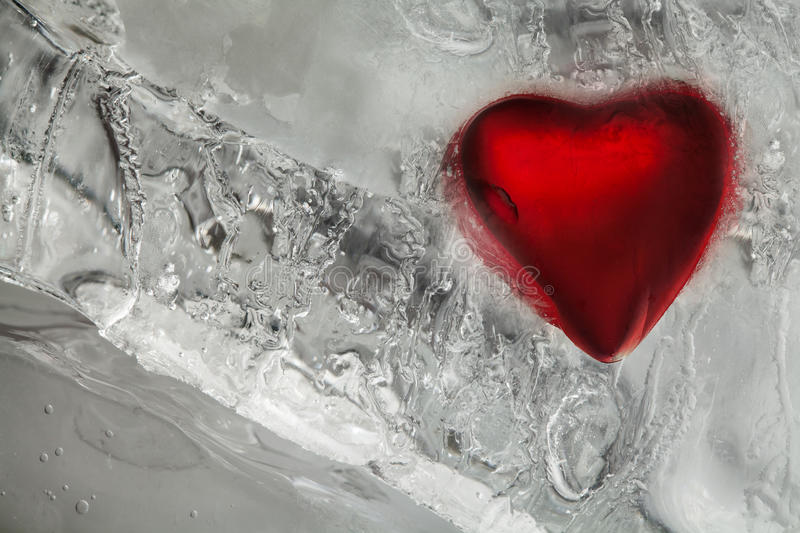 Frozen love heart in ice. Red color and frost textured pattern. Valentines day, cold winter weather background. Macro royalty free stock photo