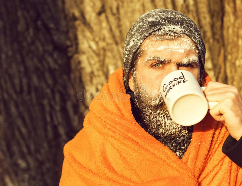 Frozen man, bearded hipster, with beard and moustache covered with white frost wrapped in orange blanket with warming royalty free stock images