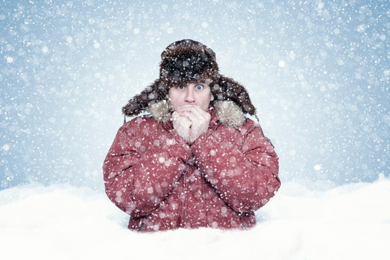 Frozen man in red winter clothes stands waist-deep in a snowdrift and warms his hands, cold, snow, frost, blizzard stock image
