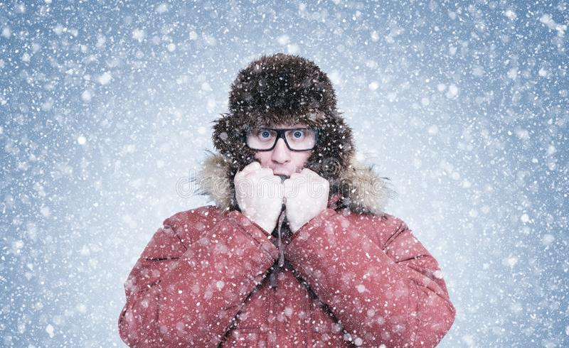 Frozen man in red winter clothes warming hands, cold, snow, frost, blizzard royalty free stock images