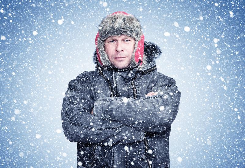 Frozen man in a sheepskin coat and hat warms his hands, cold, snow, frost, blizzard. Background stock photo