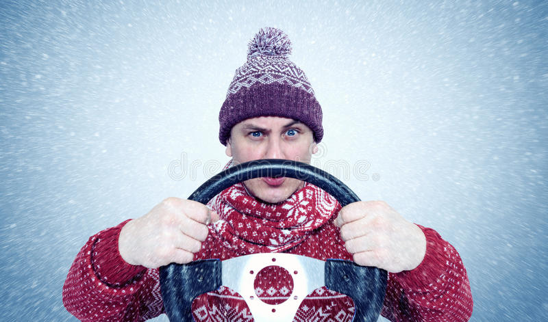 Frozen Man in sweater and hat with a steering wheel, snow blizzard. Concept car driver. stock image