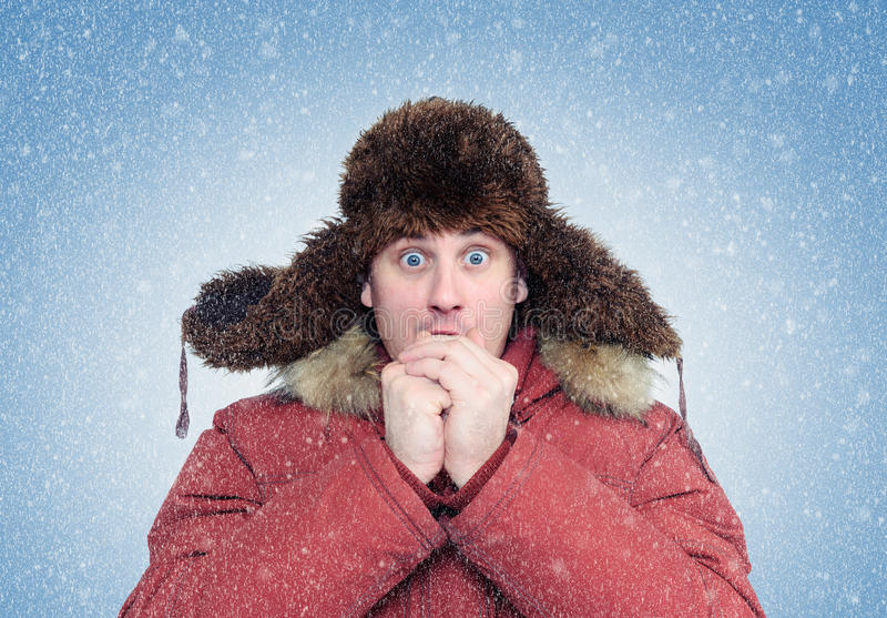 Frozen man in winter clothes warming hands, cold, snow, blizzard royalty free stock photo