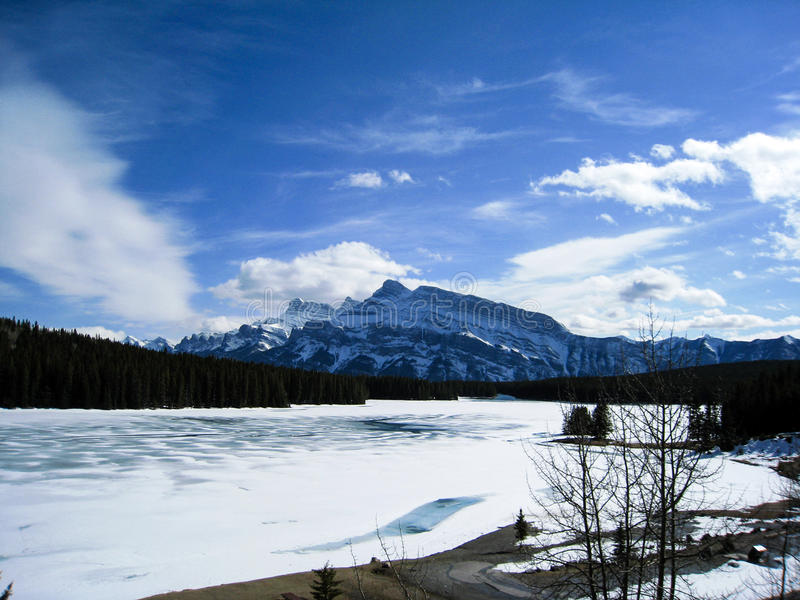 Frozen Minnewanka Lake of Banff National Park. One fine day at frozen Minnewanka Lake with blue sky in early spring royalty free stock photo