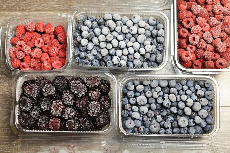 Frozen mixed berries in plastic containers, preserved forest fruits for winter time royalty free stock photography
