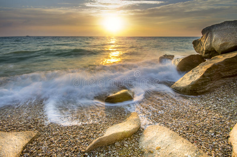Frozen moment wave enveloping the stone on the seashore. A frozen moment wave enveloping the stone on the seashore royalty free stock photo