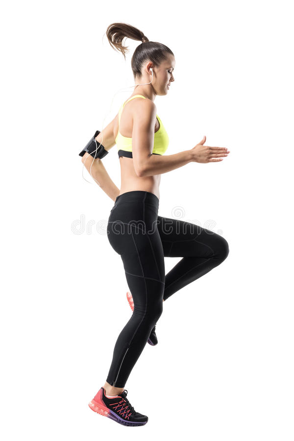 Frozen motion of fit female athletic runner doing high knees warm up exercise. Full body length portrait isolated on white studio background stock photo