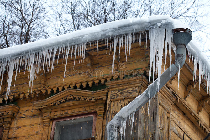 Frozen mysterious mansion with water pipe and icicles on the roof, top floor. Frozen mysterious mansion with water pipe and frozen icicles on the roof, top royalty free stock image