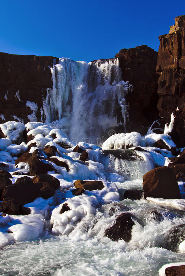 Frozen Oxararfoss Waterfall. Frozen Ice with water fron the Oxara river pouring over the Oxararfoss Waterfall, Pingvellir, Iceland stock photo