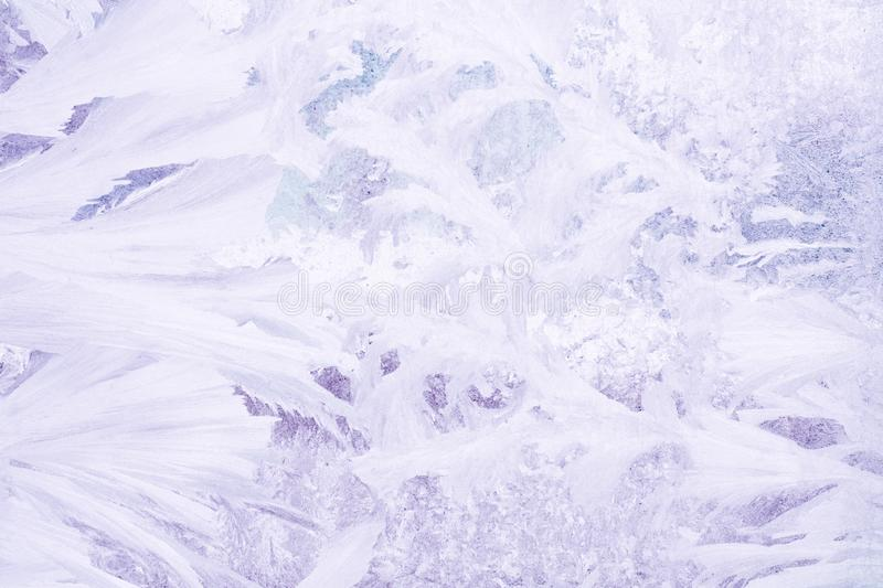 Frozen pattern on the window glass in the winter and tinted in purple.  stock images
