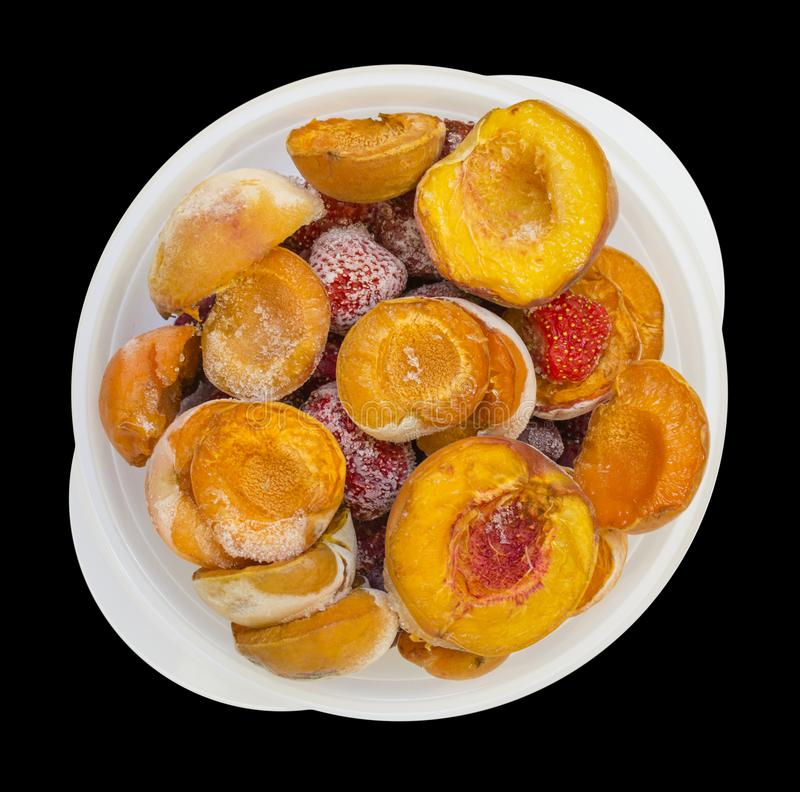 Frozen peaches apricot strawberries in a bowl isolated on black. Background photo food royalty free stock photos