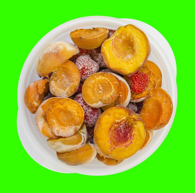 Frozen peaches apricot strawberries in a bowl isolated on green. Background photo food stock photo
