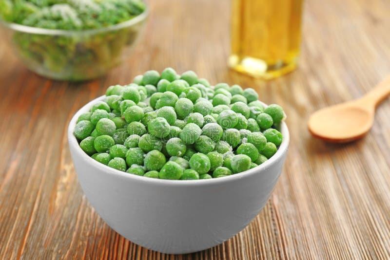 Frozen peas in bowl stock photos