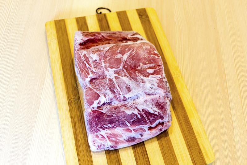 Frozen piece of meat on the table. stock photos