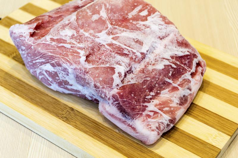Frozen piece of meat on the table. stock photo
