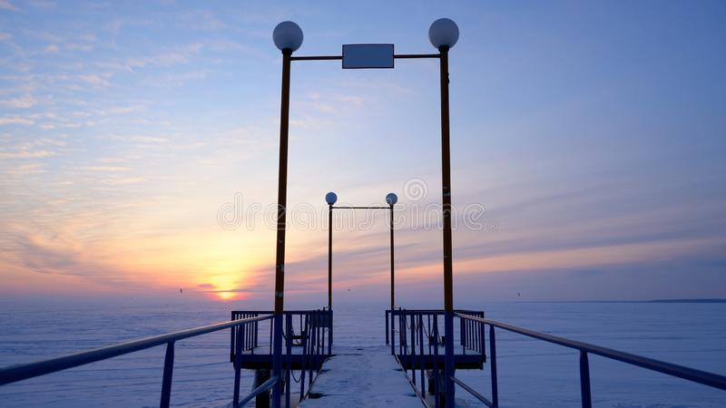 A frozen pier against the backdrop of an icy snow-covered field. And a beautiful sunset stock image