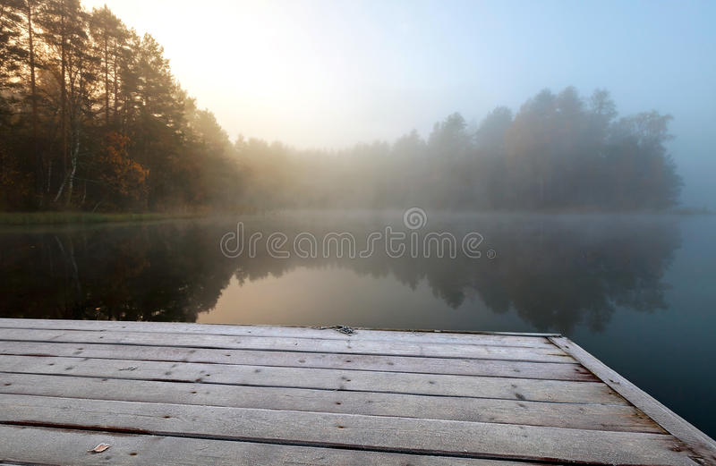 Frozen pier on lake in cold still foggy morning stock photos
