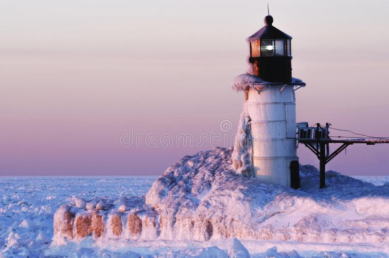 Frozen Pink Lighthouse on Lake Michigan. This ice covered lighthouse along Lake Michigan is pink and blue from the colors of a nearly set sun. Located in Saint stock photo