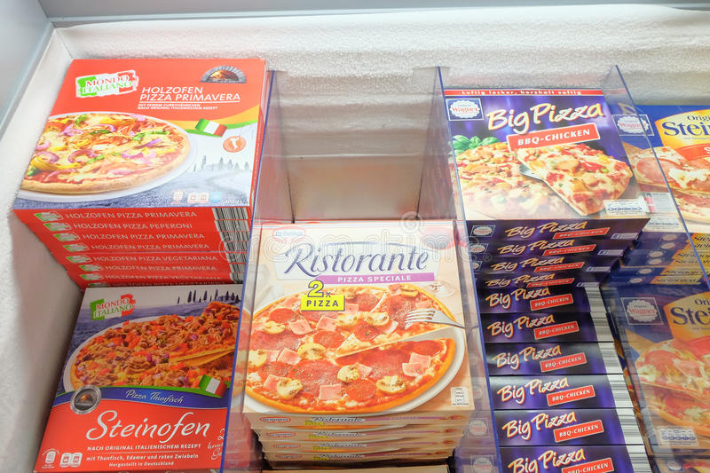 Frozen pizzas. In the frozen food section of a supermarket - focus is best at the bottom, as it is closer to you stock photo